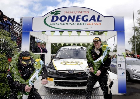Winning driver Sam Moffett, showers his co-driver James O'Reilly with champagne on the finish ramp in Letterkenny, yesterday. Photo: Declan Doherty.