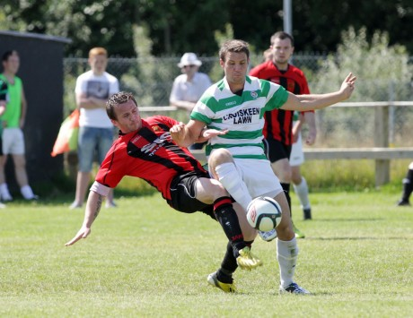 Kildrum Tigers Ronan Coyle gets the challenge in against Malachy McDermott of Cockhill Celtic. Photo: Donna McBride