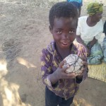 A young boy holds the ball made of plastic bags. The children were overjoyed when the group from Rathmullan brought them a proper football to play with.