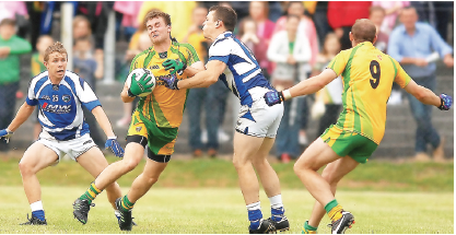 Eamon McGee finds his way forward blocked by Laois defender Kieran Lillis as Neil Gallagher is available for a pass.