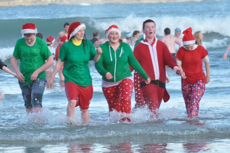 Swimmers in Christmas costumes at the Annual New Year's Swim at Marble Hill Beach.