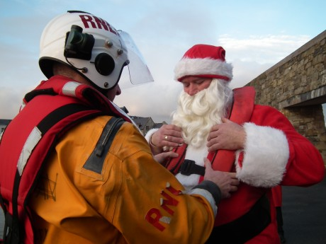 Santa gets helped into his lifejacket.