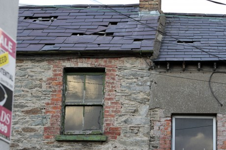 Loose slates and holes in the roof of a house on Church Lane.