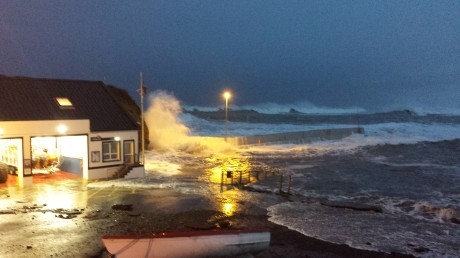 The scene at 8am on Saturday morning as the tide continues to breach the wall.