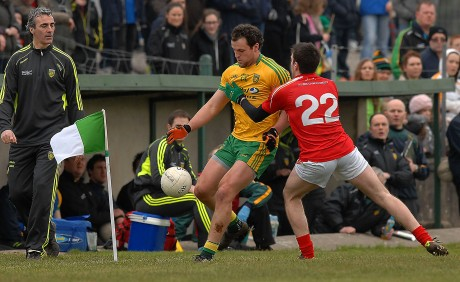 Michael Murphy gets his kick off to a team mate as manager Jim Mc Guinness looks on, in the league game in Fr. Tierney Park, Ballyshannon.