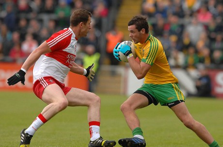 Odhran MacNiallais, taking on Patsy Bradley, Derry, as he sets his team on the attack.