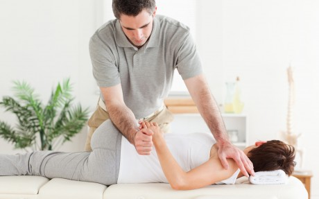 Masseur stretching woman's arm