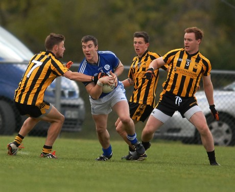 Leo McLoone on the burst for Naomh Conaill as Sean McVeigh and Eamonn Doherty of St Eunans, move in to halt his run.