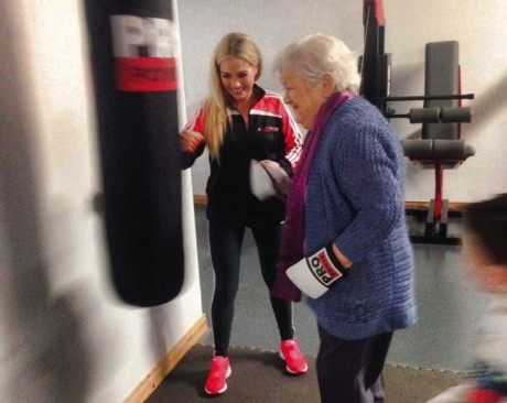 Aoife McGill at the launch of her new business with her granny giving it socks on the punch bag.
