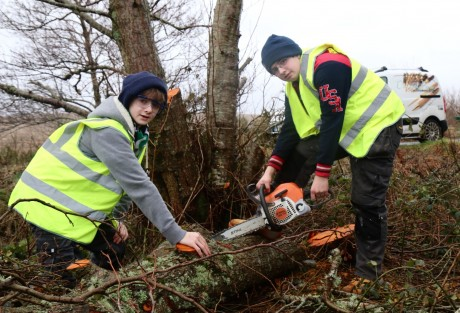 Ronan and Conor with a tree blown down in Storm Rachel.(Non-working chainsaw used as a photo prop only).