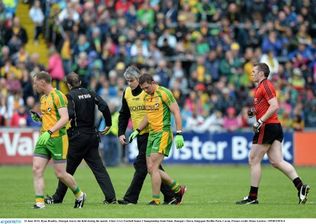 Ryan Bradley, Donegal, leaves the field during the 2013 Ulster semi-final against Down. Dr Charlie McManus is accompanying the player.