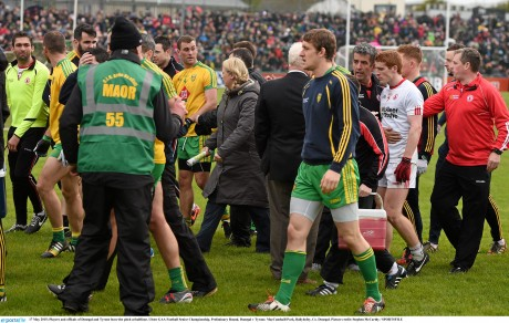 Players and officials of Donegal and Tyrone leave the pitch at half-time