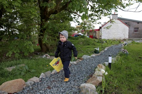 Fergus wanders the garden with the restored and extended cottage in the background.