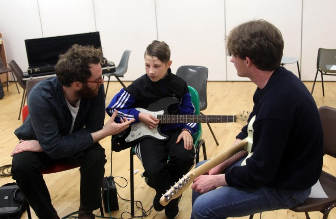 Ruairi Friel and Charlie Doherty with guitar pupil Reelan McHugh. Photos: Donna El Assaad
