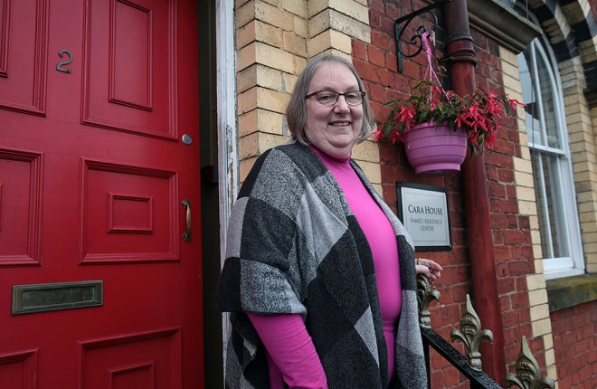 Founder, Susan-McCauley at the famous red door of Cara House.