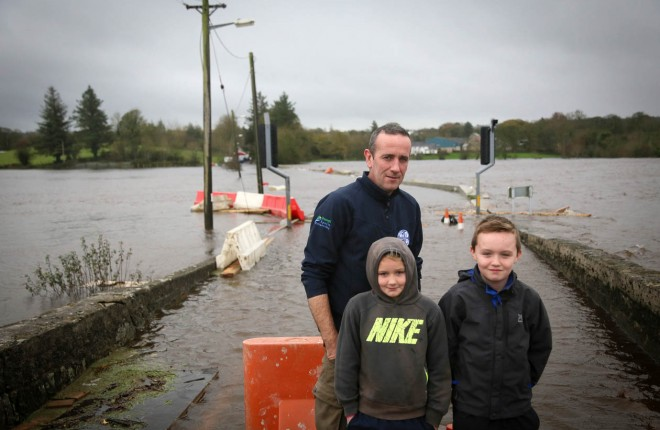 Aaron, Iona and Ronan McDaid at the almost submerged Castlefinn Bridge today. This is their normal route home. Picture: Brian McDaid.