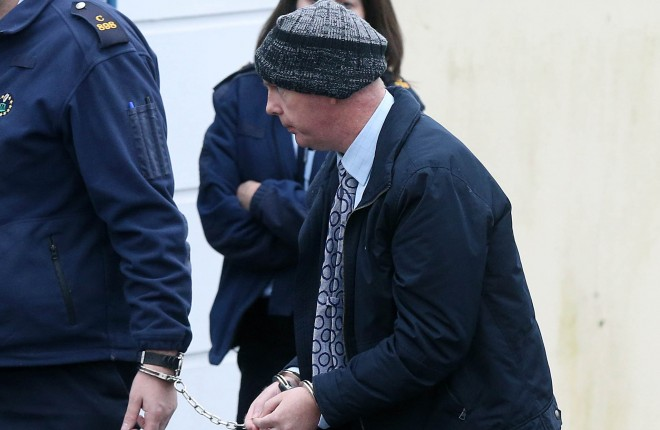 Julian Cuddihy is led into Letterkenny District Court earlier this morning