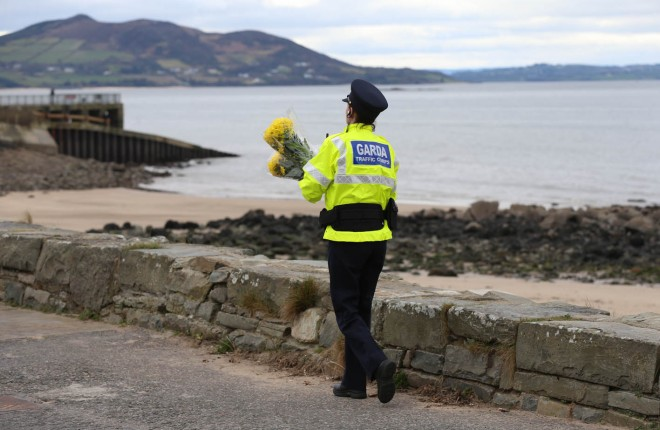 A Garda officer lays floral tributes close to where the tragedy occurred last night.