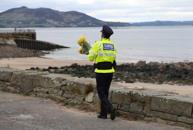 A Garda officer lays floral tributes close to where the tragedy occurred.