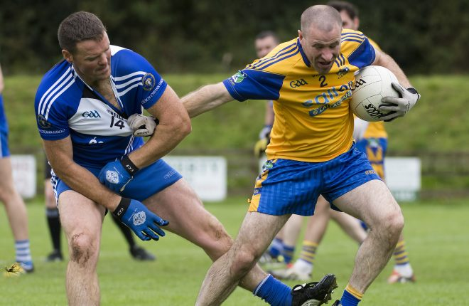 Burt's Martin Donaghey holds off the attentions of Cloughaneely's Sean Maguire during Saturday's quarter final. Photo Evan Logan