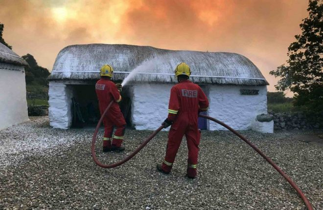 Firefighters spray foam on to the roofs of thatched cottages to protect them from a nearby wild fire. Photos: Buncrana Fire and Rescue Service.
