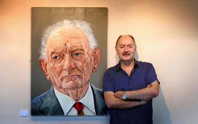 Philip Mackey beside his portrait of the late playwright Brian Friel.